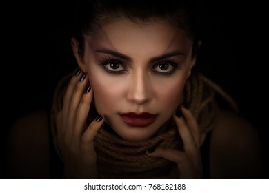 Portrait of young woman over rope with black background. Fashion, extraordinary makeup and face lifting concept.