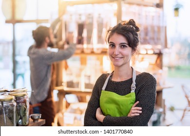 Portrait of a young woman owner of her food store. She is looking at the camera, arms crossed