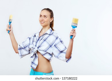 Portrait of young woman with paint brushes