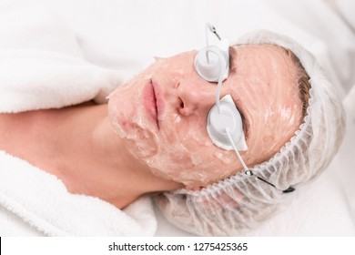 Portrait of a young woman patient. Anti acne phototherapy with professional equipment. Beautiful woman during photo rejuvenation procedure. Face skin treatment at cosmetic clinic.