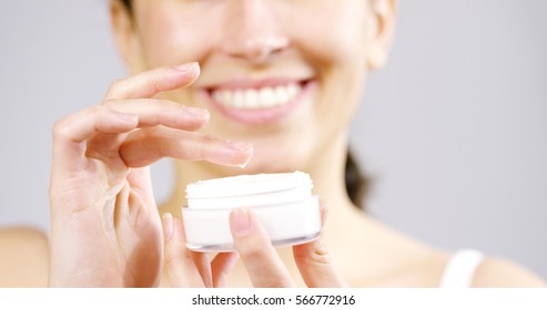 The portrait of young woman with perfect skin applying a day/night cream on her previously cleansed face. Concept of skincare, cosmetics, beauty, wellness center, facial treatment, facial massage