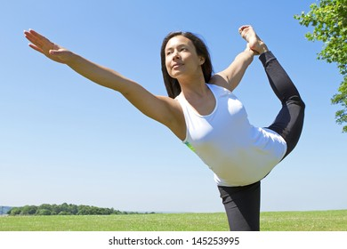 Portrait of a Young Woman performing Yoga outdoors in the country side