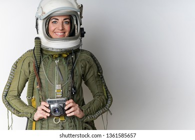 Portrait of a young woman pilot of airplane and astronaut with helmet and suit on an isolated white background
