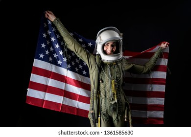 Portrait of a young woman pilot of plane and astronaut with flag of America, helmet and suit on an isolated black background