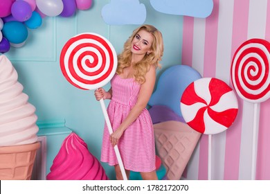 Portrait of young woman in pink dress holding big candy cane and posing on decorated background.