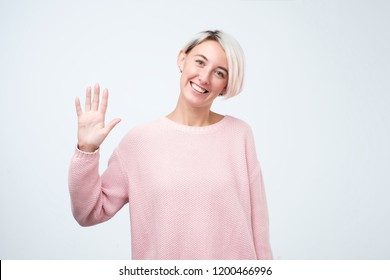 Portrait of a young woman in pink sweater smiling and saying hello. I am so glad to see you