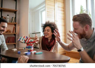 Portrait of young woman playing a game with friends at home.