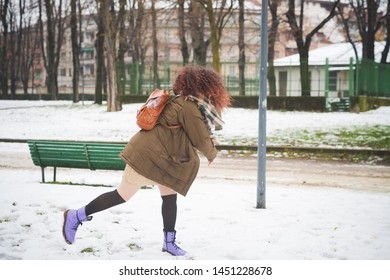 portrait of young woman playing in park with snowball – movement, happiness, new generation