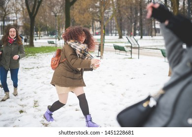 portrait of young woman playing in park with snowball – movement, happiness, friendship