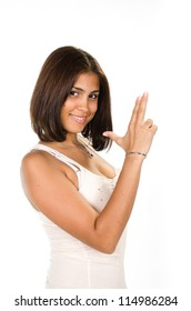 Portrait of young woman pointing away  a hand gun against white background