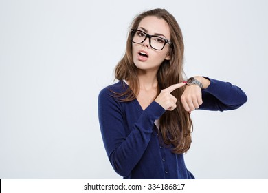 Portrait of a young woman pointing finger on wrist watch isolated on a white background