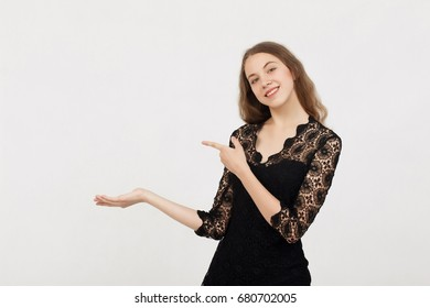 Portrait of young woman pointing hands finger at corner with copyspace isolated on a white background.Woman with finger point up