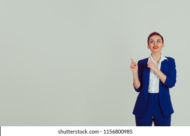 Portrait young woman pointing with index fingers up to the copy space isolated on gray wall background. Positive face expression body language life perception