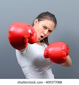 Portrait of young woman posing with boxing gloves against gray background