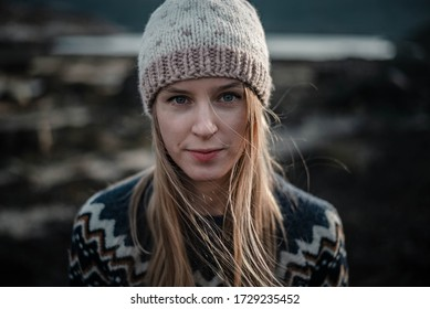 Portrait of a young woman posing in handmade knitted hat. Natural blonde haired woman looking to a camera