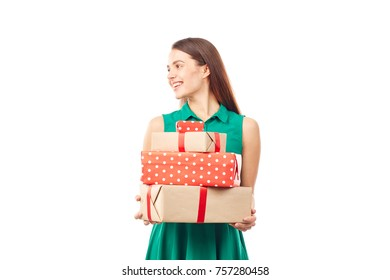 Portrait of young woman posing with heap of gift boxes on white background