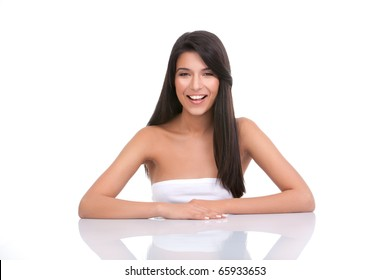 a portrait of a young woman, posing on a white background. she has her arms on a white table; she has a wide smile and a relaxed face expression.