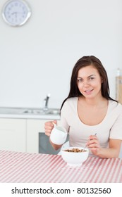 Portrait of a young woman pouring milk in her cereal in her kitchen