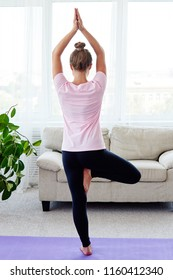 Portrait of young woman practicing balance yoga asana Vrikshasana at home indoor, copy space, back view. Girl doing tree pose, full length. Relaxing and doing yoga. Wellness and healthy lifestyle