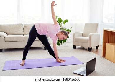 Portrait of young woman practicing yoga at home indoor, copy space. Girl stretching on mat, full length. Utthita trikonasana exercise, triangle pose. Wellness and healthy lifestyle