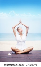 Portrait of a  young woman practicing yoga at the beach