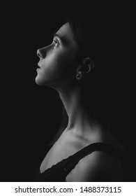 Portrait of young woman in profile. Low key. Black and white.