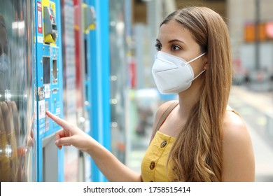 Portrait of young woman with protective mask KN95 FFP2 choosing a snack or drink at vending machine in train station. Vending machine with girl.