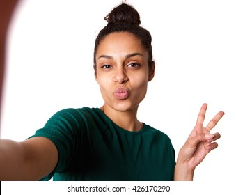 Portrait of young woman with puckering lips and peace hand sign taking selfie against white background