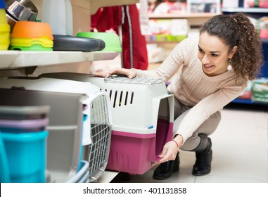 Portrait of young woman purchasing pet kennels in petshop