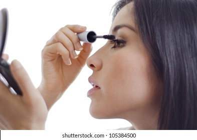 Portrait of young woman putting some mascara on and getting ready