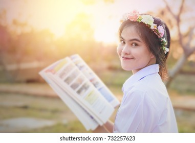 Portrait of young woman reading a book at garden, thai student