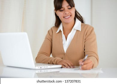 Portrait of a young woman reading documents and using her laptop