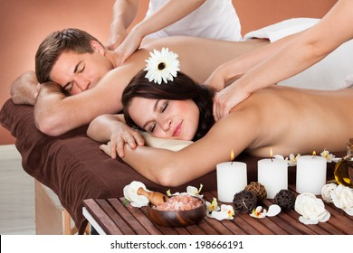 Portrait of young woman receiving shoulder massage with man in background at spa
