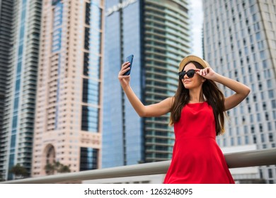 Portrait of young woman in red dress, sunglasses and summer hat make selfie or video call on the phone on downtown skycrapers background