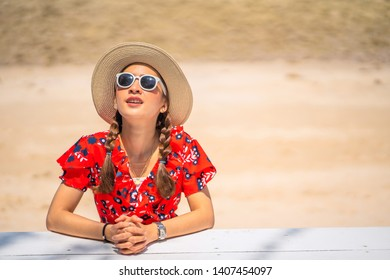 portrait Young woman in a red dress and sunglasses and hat posing on the tropical beautiful beach Travel and Vacation. Freedom and relax Concept.