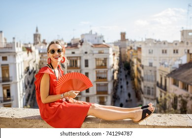 Portrait of a young woman in red dress with hand fan sitting with beautiful cityscape on the background in Valencia, Spain