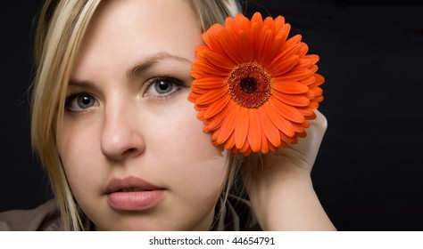 Portrait young woman with red flower on black background