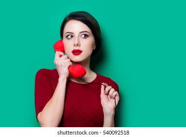 Portrait of young woman with red handset on green background