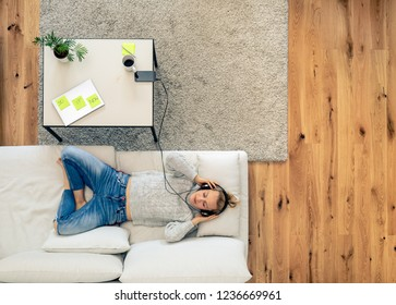 Portrait of a young woman relaxing on couch and listening to music using smart phone and headphones. Home office break with laptop computer and coffee waiting on a table.