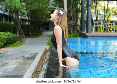 portrait of young woman relaxing in swimming pool, enjoy weather in tropical country on background of apartment building on sunny day with sunshine. Concept of enjoying life, tratement for healthy