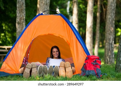 Portrait of young woman relaxing in a tent while camping with friends