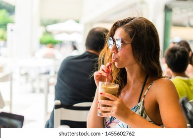 Portrait of young woman at the restaurant drinking frappe coffee in a summer day on the vacation wearing sunglasses