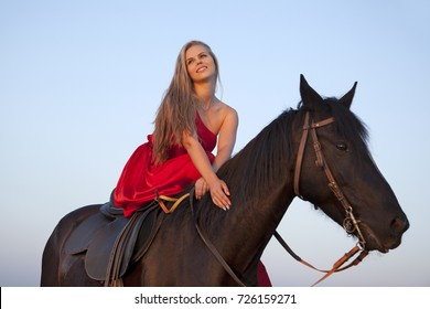 Portrait of a young woman riding a horse. Bottom-up view. Blonde in a red dress smiling on blue sky background