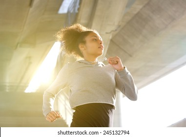 Portrait of a young woman running in urban environment