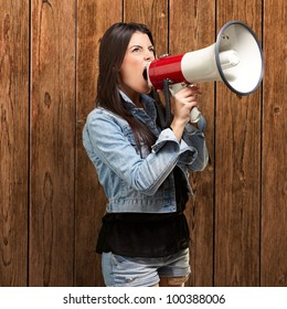portrait of a young woman screaming with a megaphone against a wooden wall