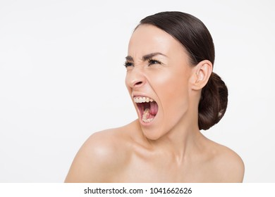 Portrait of a young woman screaming sideways with anger.