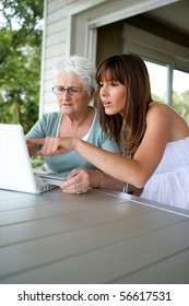 Portrait of a young woman and a senior woman with a credit card in front of a laptop computer