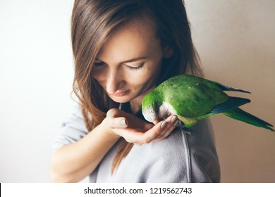 Portrait of young woman with shaming and friendly Monk parakeet parrot who is sitting on her shoulder and eating food from her hand. Film effect. Selective focus. Natural light shoot.
