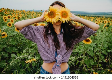 Portrait of a young woman in a shirt in the field, a woman closes her eyes with sunflowers.