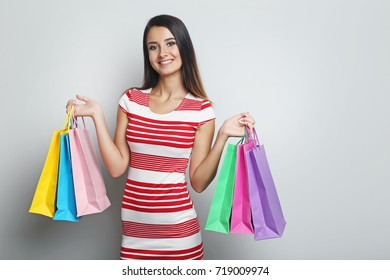 Portrait of young woman with shopping bags on grey background